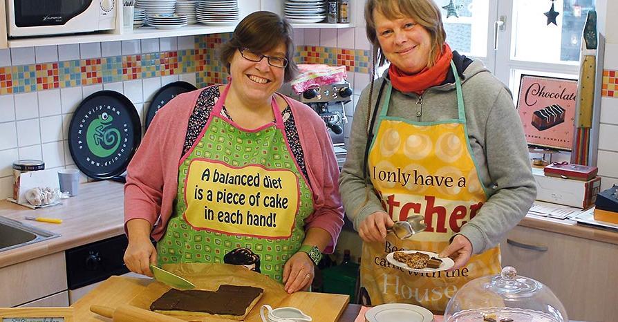 Leckeres von der Insel: Petra von Schwanenflug (links) und Beate Ludwig schneiden in der Küche ihres Ladens einen selbstgebackenen Kuchen an.