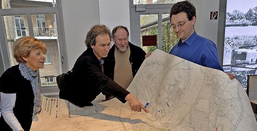 Martin Schramm (v.re.), Hermann Huber und Barbara Ohm haben als Team den Teppich erstellt. Stadtheimatpfleger Alexander Mayer begutachtet interessiert das Werk.