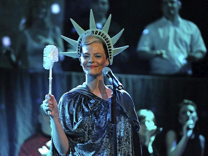 Miss Liberty gibt mit der Klobürste den Takt vor.