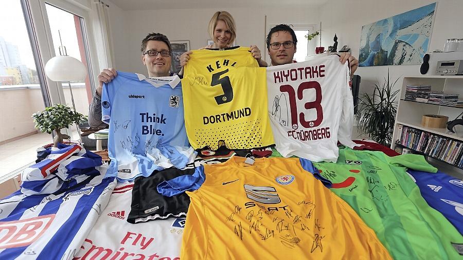 Eine gute Idee: Jens Möller, Sandra Böck und Thomas Rudolf (von links) präsentieren Trikots von Fußballern — Shirts und Fußballschuhe werden für einen guten Zweck im Netz versteigert.