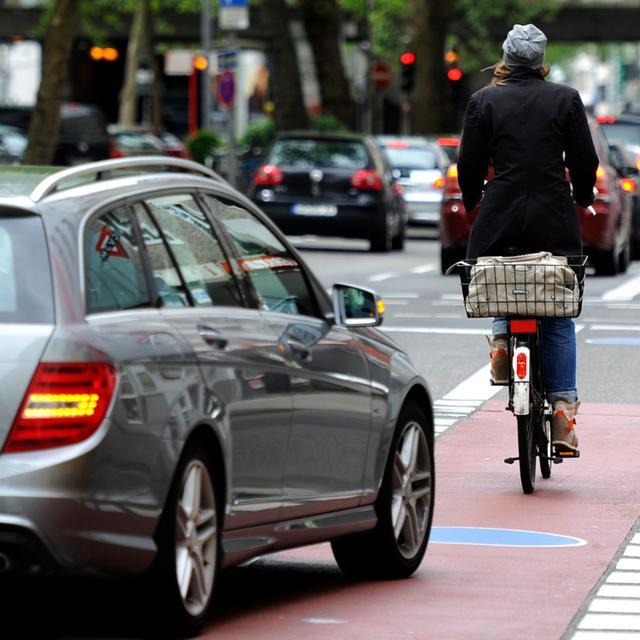 Eine Frau fährt am 11.05.2013 mit ihrem Fahrrad neben Autos auf einer Straße in  Köln (Nordrhein-Westfalen). Am 13.05.2013 beginnt in Münster der 3. Nationale  Radverkehrskongress. Foto: Marius Becker/dpa (zu dpa-Interview