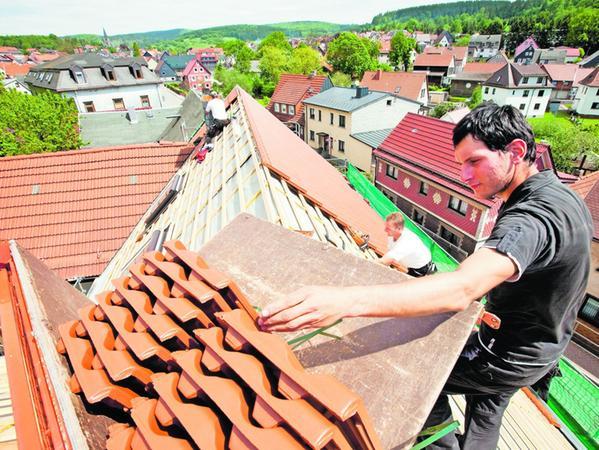 Der Dachdeckern Oliver John reicht einige Dachziegel zum Legen zu, aufgenommen am 03.06.2010. Die Dachdecker nutzen das gute Wetter, um dem zu sanierenden historischen Fachwerkhaus von 1717 in Brotterode ein neues Dach zu geben. Foto: Michael Reichel dpa/lth +++(c) dpa - Bildfunk+++