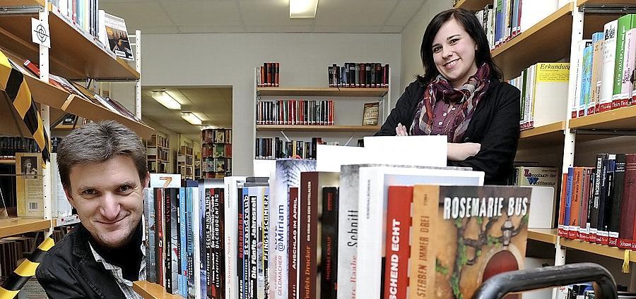 Büchereileiterin Christina Röschlein freut sich über eine Literaturspende des Fürther Krimiautors Veit Bronnenmeyer.