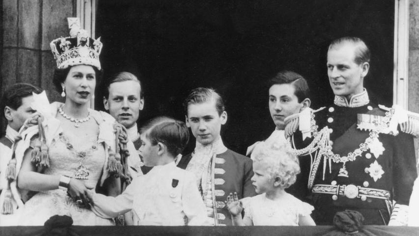Königin Elizabeth II. von Großbritannien mit der St. Edward's-Krone auf dem Haupt und den Kindern Prinz Charles, Prinzessin Anne und ihr Gatte Prinz Philip, Herzog von Edinburgh, auf dem Balkon des Buckingham Palastes kurz nach der Krönungszeremonie am 2. Juni 1953 in London.