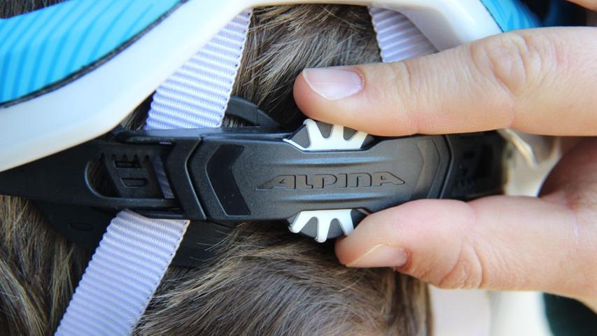 Der Helm soll fest am Kopf sitzen, ohne zu drücken. Das lässt sich per Rädchen über dem Nackenbereich einstellen. Der Helm sollte da natürlich schon auf dem Kopf sitzen.