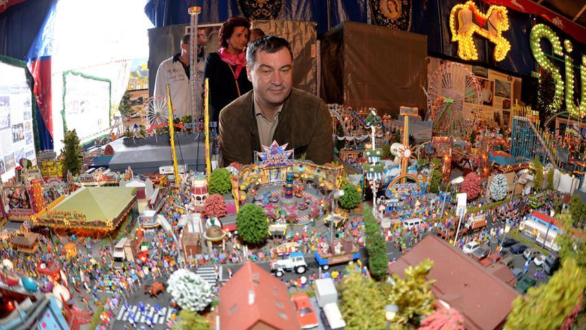 Etwas melancholisch blickt Bayerns Finanzminister auf die Miniaturausführung des Nürnberger Volksfests. Ob da wohl gerade Kindheitserinnerungen wach werden?