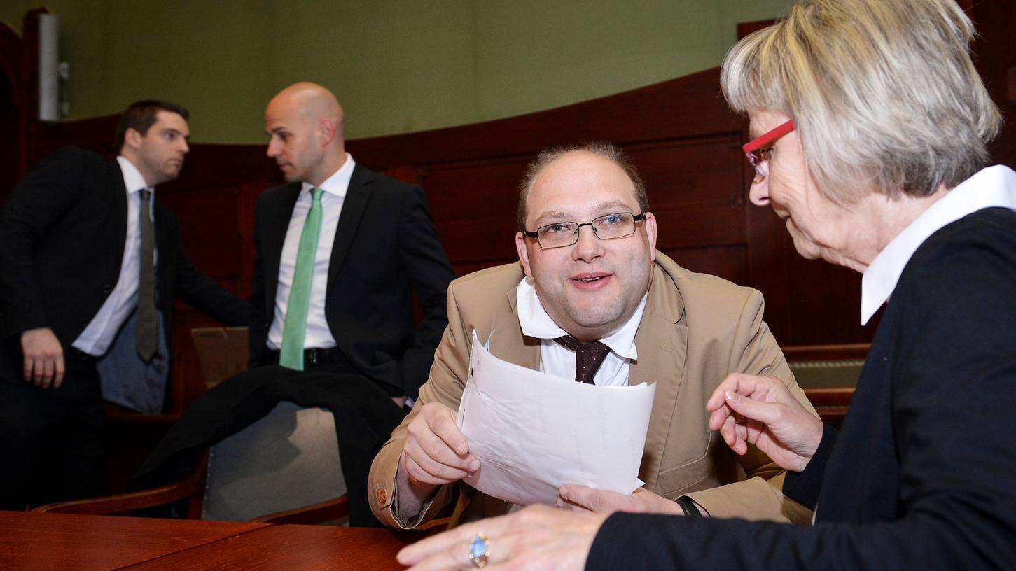 Ulvi Kulac (Mitte) zeigt seiner Betreuerin Gudrun Rödel Dankesbriefe, die er persönlich an seine Unterstützer verfasst hat, während sich sein Anwalt Michael Euler (links) mit einem weiteren Verteidiger bespricht.