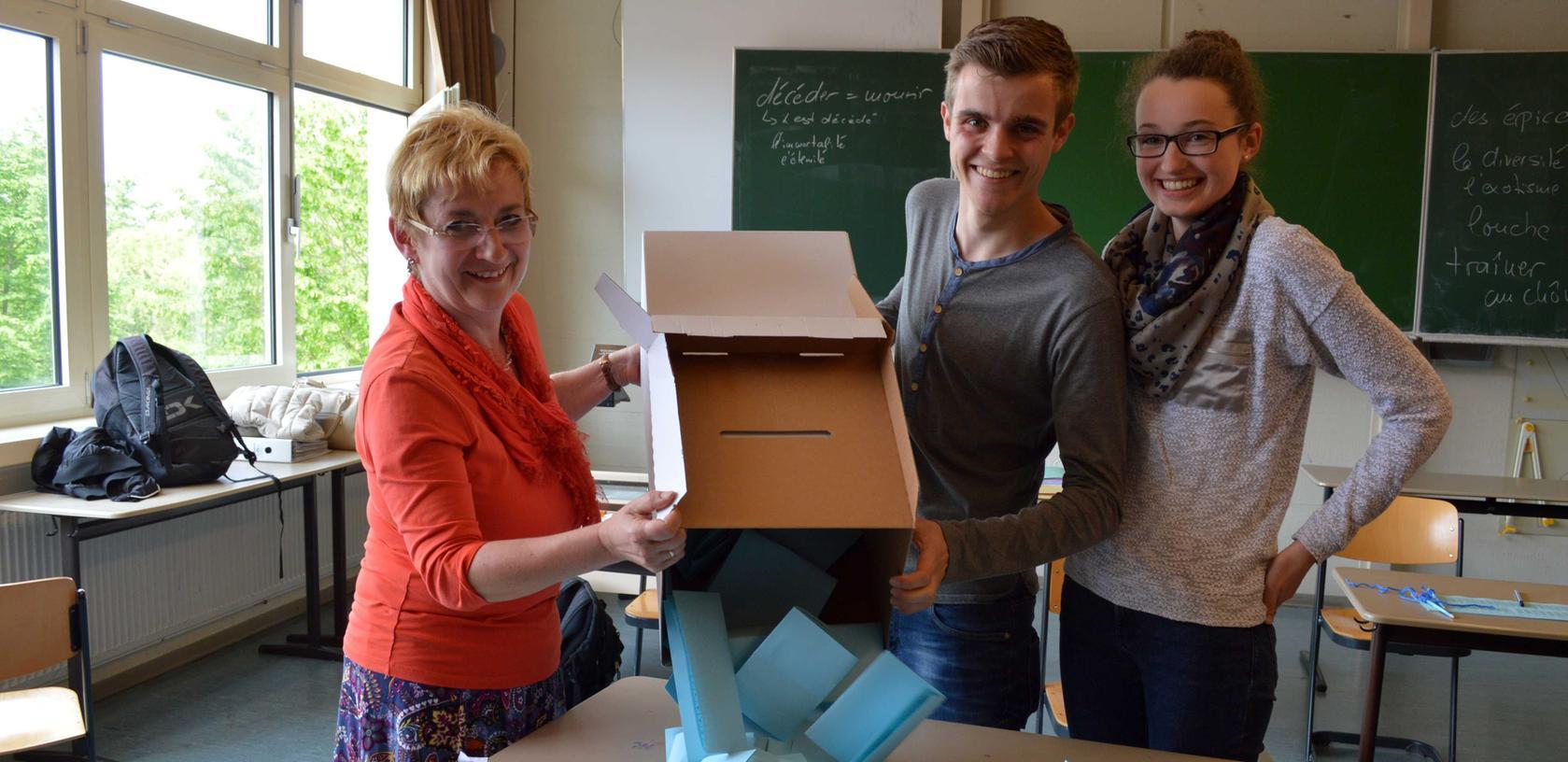 Die Auszählung kann beginnen: Birgit Arnold, Lehrerin am Wolfgang-Borchert-Gymnasium in Langenzenn, leert die Urne mit Kevin Rösch und Laura Gimperlein. (v.li.n.re.)