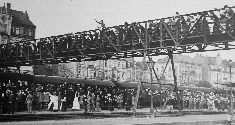 Eine große Menschenmenge verabschiedet zu Kriegsbeginn einen Truppentransport am Fürther Hauptbahnhof. Auch der 1922 eingestürzte Fußgängersteg zwischen Bahnhofplatz und Karolinenstraße war dicht bevölkert. Weniger enthusiastisch werden später die Rücktransporte der Verwundeten empfangen.