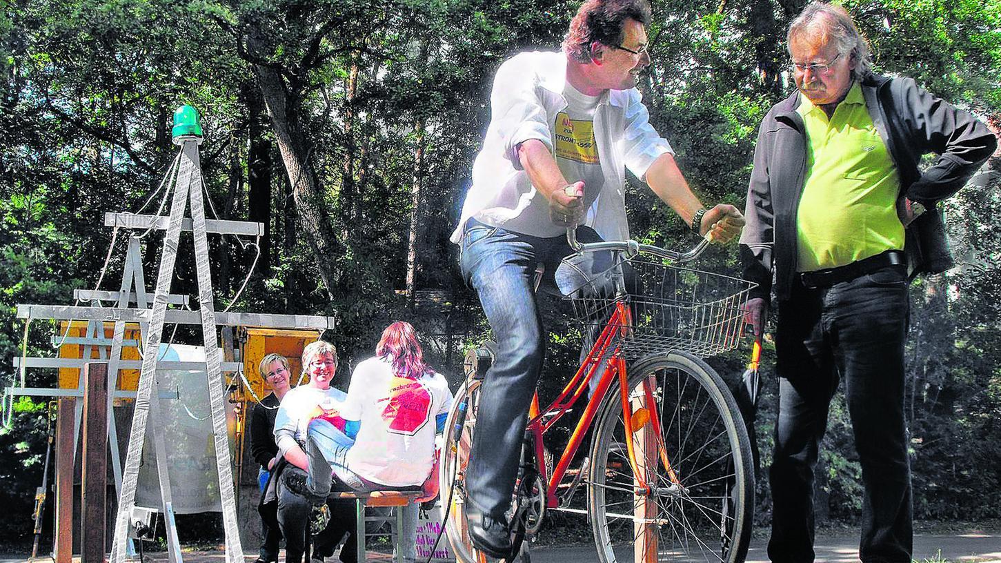 Zum Protestradeln auf einem Stromrad wurde in Raitersaich eingeladen. Entworfen hatten es Roßtals Umweltreferent Michael Brak (re.) und Andrea Platzer von der BI Stromtrassenwiderstand, gemeinsam mit der Kärwa-Jugend.