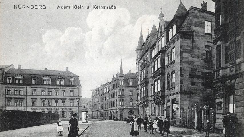 Bürger stehen im Jahr 1910 in der Nähe eines Kaufhauses in der Adam-Klein-Straße.
