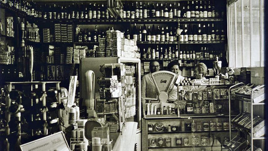 """Unter dem Titel """"Unbekanntes Treuchtlingen"""" zeigt der Treuchtlinger Kurier in Zusammenarbeit mit dem Volkskundemuseum Fotos aus Treuchtlingen und Umgebung aus mehr als 100 Jahren. Hier ist das Drogerie- und Lebensmittelgeschäft von Karl und Erna Poujol zu sehen, die darauf zusammen mit einer Angestellten abgebildet sind. Die Drogerie wurde in den 30er Jahren des vorigen Jahrhunderts von Poujols Eltern gegründet. Damals war es noch üblich, viele Waren offen zu verkaufen, also aus großen Gebinden, zum Beispiel auch Zucker und Mehl. Auch wurden Essig und Speiseöl noch offen verkauft und erst im Ladengeschäft in die Gefäße der Kunden abgefüllt."""