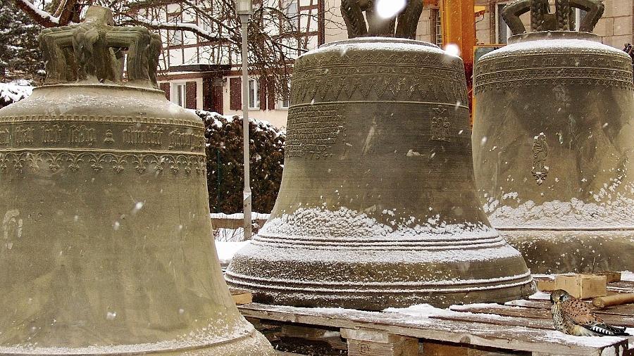 """Unser Bild zeigt die drei Glocken der Schwander Johanneskirche im Januar 2004, bevor sie zur """"Runderneuerung"""" nach Nördlingen gebracht wurden. Interessant an diesem Bild: Rechts vorne auf der Palette sitzt der Turmfalke, der im Glockenturm nistet. Er ist wohl """"seinen"""" Glocken vom Turm hinab auf den Kirchhof gefolgt."""
