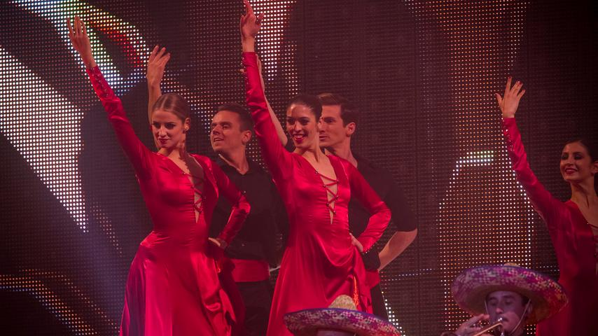 In feurigem Rot heizen diese Tänzerinnen der Menge ein.