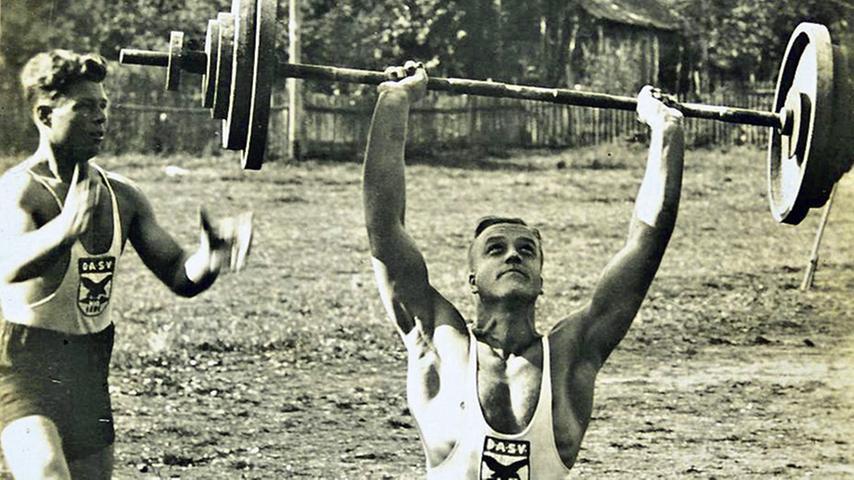 Auf die Frage nach den Namen der zwei Gewichtheber, die auf diesem Foto auf dem Platz vor der damaligen Turnhalle zu sehen sind, sowie nach der Geschichte des Vereins DASV 1894 antwortete unsere Leserin Helga Pfahler. Der Mann mit den Gewichten ist Hermann Neumeyer, der Bruder des ehemaligen Bergsteigers. Er war Bäcker bei der Konditorei Stegmeier in der Bahnhofstraße. Das Bild muss vor 1936 aufgenommen worden sein, denn der DASV (Deutscher Athletik Sportverband), dessen Vereinswappen klar zu erkennen ist, wurde im Rahmen der Gleichschaltung durch die Nazionalsozialisten verboten. Der DASV stammte aus der Arbeiterbewegung. Neumeyer arbeitete später bei Krauss-Maffei. Der Ahtlet links ist Ernst Drießlein, Jahgang 1904. Dies wurde uns von dessen Sohn Ernst mitgeteilt. Aus dem Besitz der Familie Drießlein stammt auch das Foto.