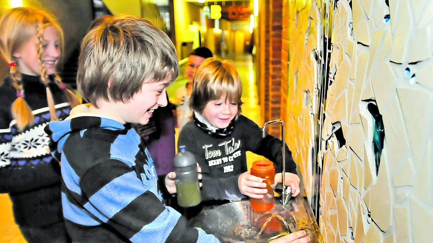 Schüler des Neuen Gymnasiums füllen am Brunnen ihre Trinkflaschen auf.