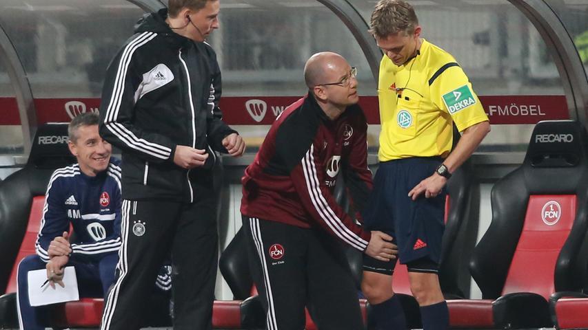 Kurze Unterbrechung: Schiedsrichter Drees hat Probleme mit dem Oberschenkel, lässt sich von FCN-Team-Arzt Brem behandeln.