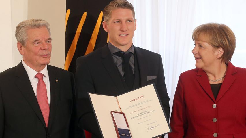 Vier Sterne sind ein Grund großer Freude: Gemeinsam mit Bundespräsident Joachim Gauck gratuliert Angela Merkel Fußball-Nationalspieler Bastian Schweinsteiger zum Gewinn der Fußball-WM 2014 in Brasilien.