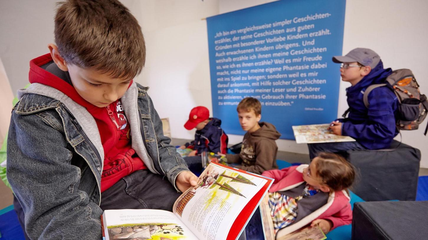 Dass Jungs so vertieft in Bücher sind, ist nicht die Regel (hier bei einer Ausstellung). Oft wird ihnen in der Schule nicht der Lesestoff geboten, der sie fesselt, klagt der Nürnberger Professor Wolfgang Tischner.
