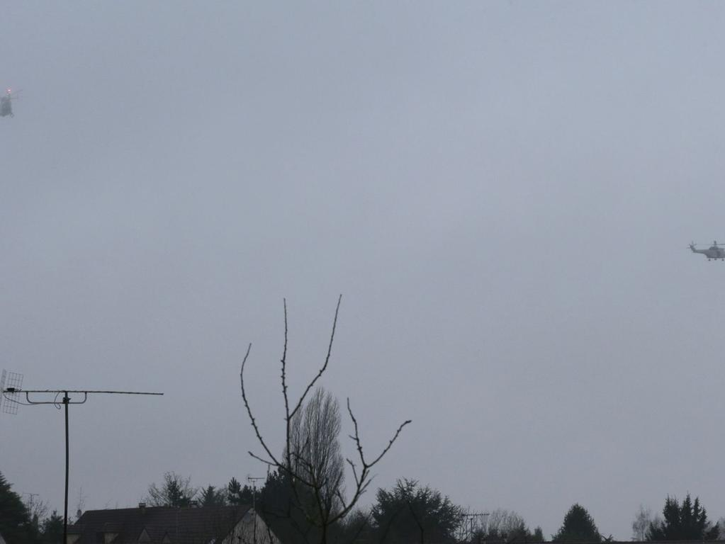 Two helicopters fly over Dammartin-en-Goele where shots were fired and at least  one hostage was taken in the same area police were hunting for two brothers  accused of slaughtering 12 people in an Islamist assault, on January 9, 2015.  The hostage drama was underway at a business in Dammartin-en-Goele, to the  north-east of Paris, and came 48 hours into a massive manhunt for the Islamist  gunmen who attacked the Charlie Hebdo offices on Wednesday. AFP PHOTO / JOEL  SAGET