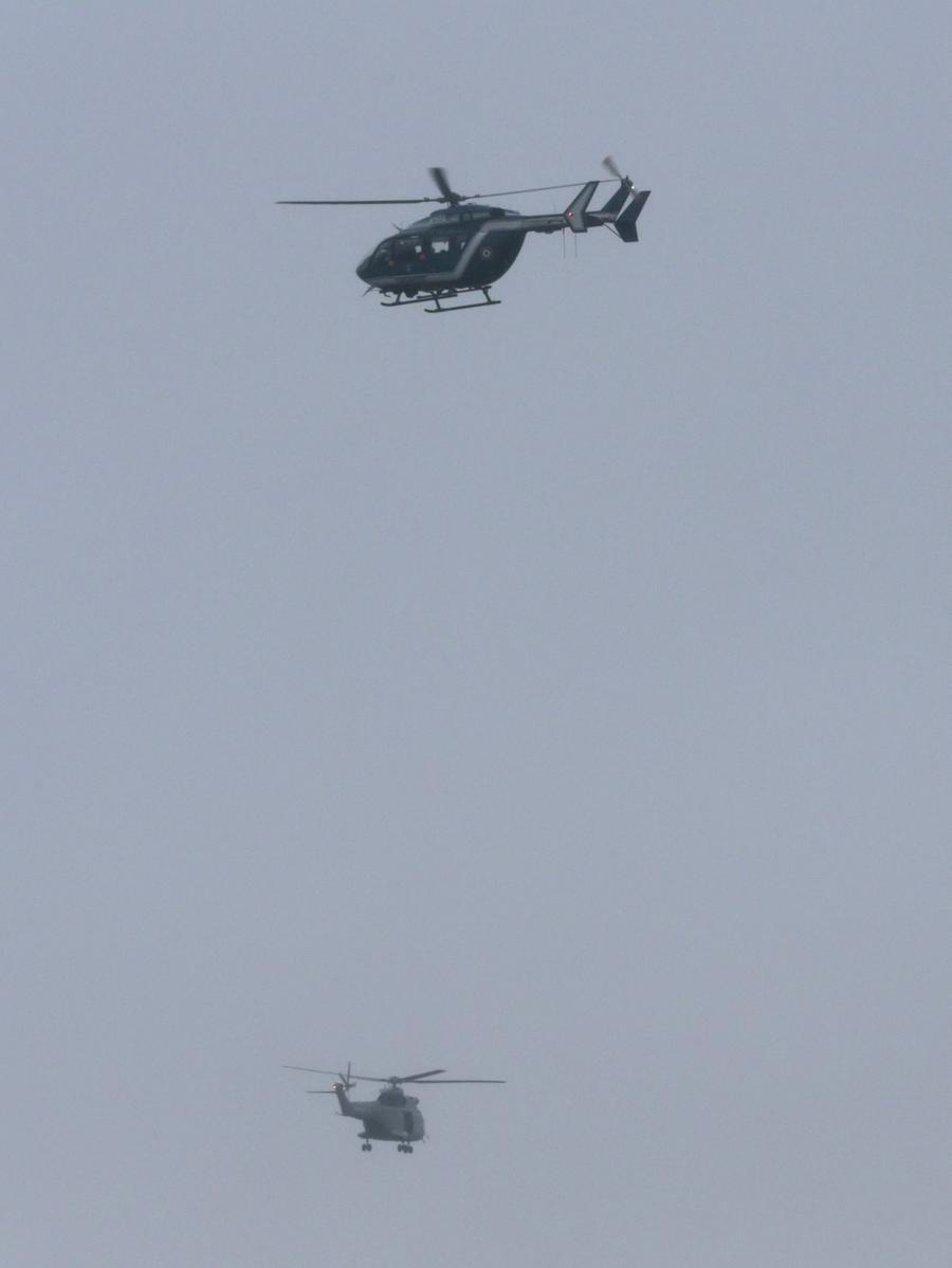 Helicopters fly over Dammartin-en-Goele where shots were fired and at least one  hostage was taken in the same area police were hunting for two brothers accused  of slaughtering 12 people in an Islamist assault, on January 9, 2015. The  hostage drama was underway at a business in Dammartin-en-Goele, to the  north-east of Paris, and came 48 hours into a massive manhunt for the Islamist  gunmen who attacked the Charlie Hebdo offices on Wednesday. The suspects were  holed up in a small printing business named CTD, a source close to the  investigation said. AFP PHOTO / JOEL SAGET