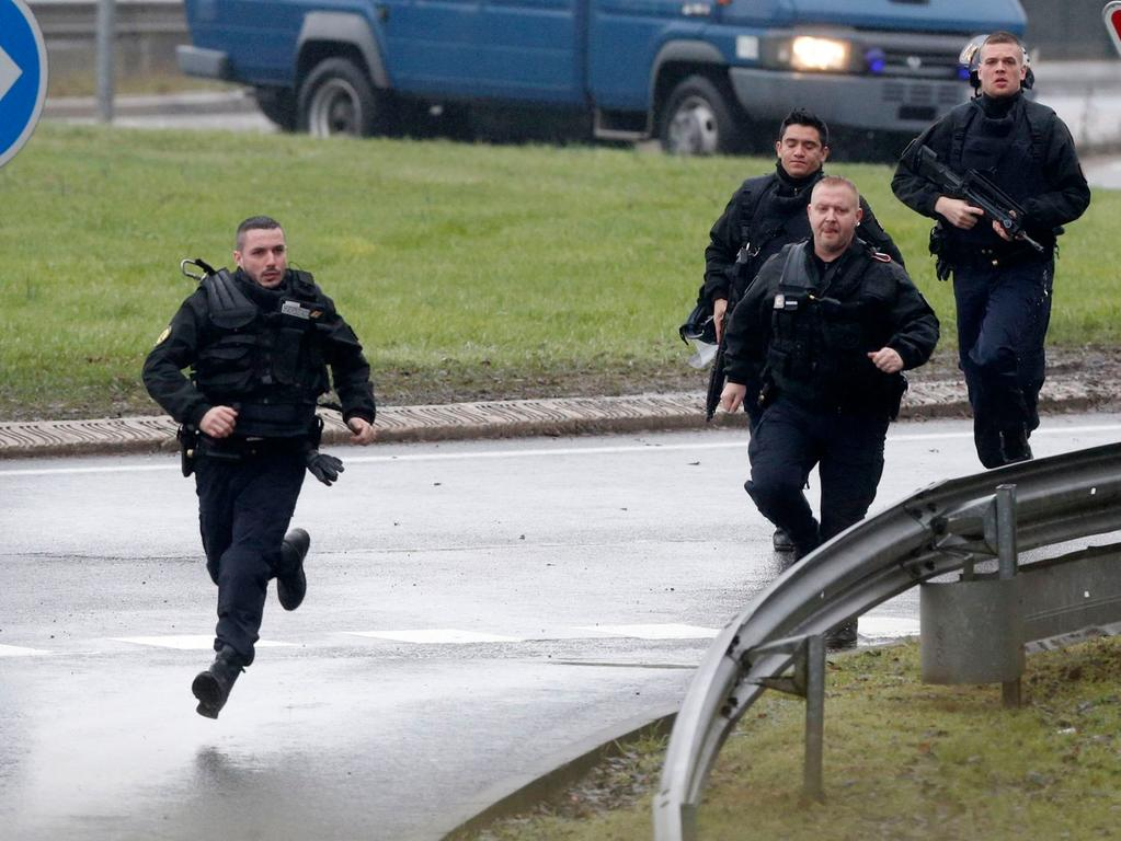 Members of the French gendarmerie intervention forces arrive at the scene of a  hostage taking at an industrial zone in Dammartin-en-Goele, northeast of Paris  January 9, 2015. The two main suspects in the weekly satirical newspaper  Charlie Hebdo killings were sighted on Friday in the northern French town of  Dammartin-en-Goele where at least one person had been taken hostage, a police  source said. REUTERS/Christian Hartmann (FRANCE - Tags: MILITARY  POLITICS)....ATTENTION EDITORS FRENCH LAW REQUIRES THAT FACES OF SPECIAL  INTERVENTION POLICE FORCES ARE MASKED IN PUBLICATIONS WITHIN FRANCE