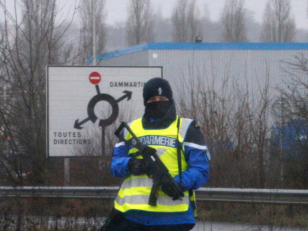 RECROP - epa04551902 A police officer stands along a road near an industrial  area where the suspects in the shooting attack at the satirical French magazine  Charlie Hebdo headquarters are reportedly holding a hostage, in  Dammartin-en-Goele, some 40 kilometres north-east of Paris, France, 09 January  2015. There has been an exchange of fire, according to media reports. EPA/YOAN  VALAT +++(c) dpa - Bildfunk+++
