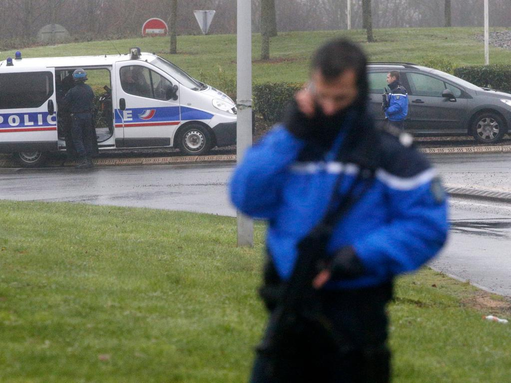 epa04551948 A police officer stands along a road near an industrial area where  the suspects in the shooting attack at the satirical French magazine Charlie  Hebdo headquarters are reportedly holding a hostage, in Dammartin-en-Goele,  some 40 kilometres north-east of Paris, France, 09 January 2015. There has been  an exchange of fire, according to media reports. EPA/YOAN VALAT +++(c) dpa -  Bildfunk+++