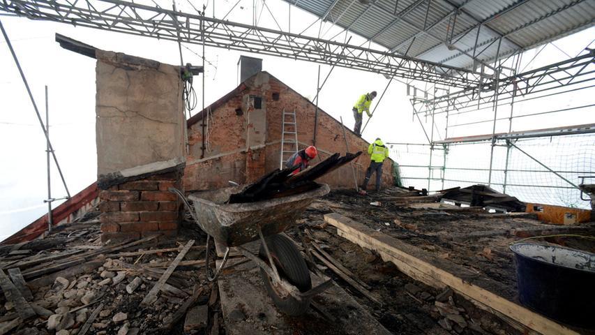 Kriegsschäden: Die verkohlten Balken sind Folge eines Bombentreffers. Für die Dauer der Arbeiten schützt ein Notdach aus Blech das Haus.