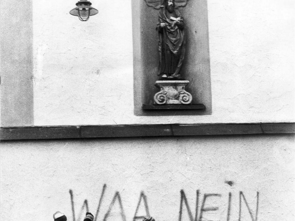 Ein kleiner Beitrag zum Protest: Kinder stehen vor dem an die Kirchenmauer gesprühten