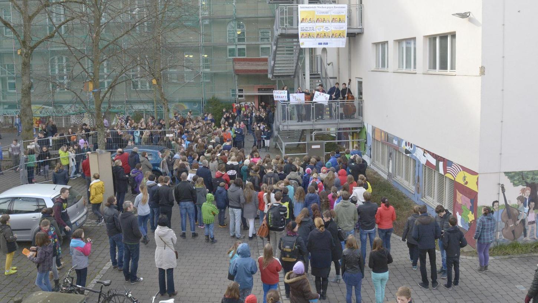 """Im Christian-Ernst-Gymnasium halten Schülerinnen und Schüler bei der Auftaktveranstaltung zu den """"Wochen gegen Rassismus"""" Schilder für mehr Toleranz und Achtung."""