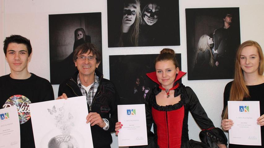 """Die Kreativen des Adam-Kraft-Gymnasiums (AKG) zeigen in einer großen Kunstausstellung im März 2015 Arbeiten aus vielen Bereichen. Die Vernissage-Besucher zeigten sich begeistert und wählten ihre Favoriten: Den ersten Preis gewann Q12-Schülerin Anne Müller (rechts), die das Thema """"Angst"""" fotografisch umgesetzt hatte. Nelli Kratz (2.v.r.) hatte ein Vampirkostüm selbst entworfen und genäht, wofür sie mit dem zweiten Preis belohnt wurde. Hannes Herzog komplettierte das Siegertrio mit einer fantasievollen Bleistiftzeichnung, Titel: """"Schlaf"""". Schulleiter Robert Scherbel gratulierte."""