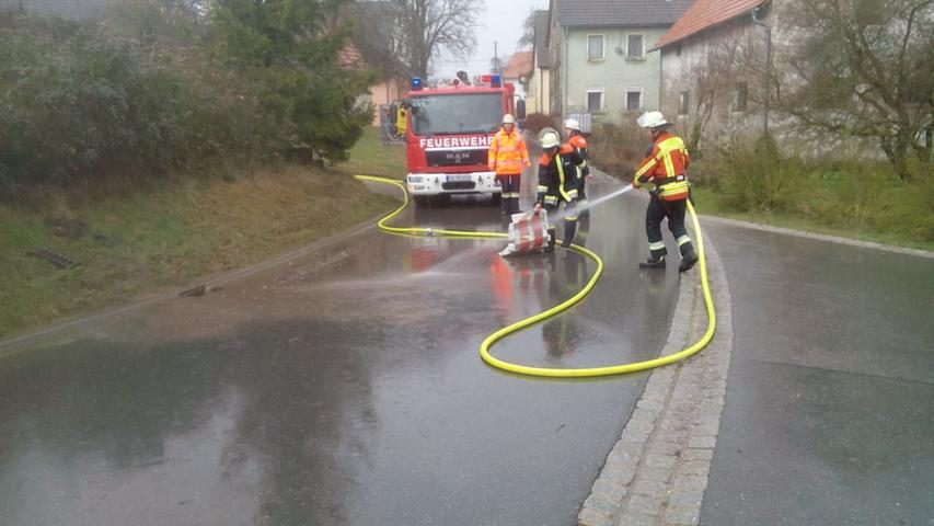 Der Starkregen hatte die Straße überschwemmt. Die Feuerwehrler beseitigten den Schmutz aus dem Kanalablauf und konnten die Straße wieder freigeben.