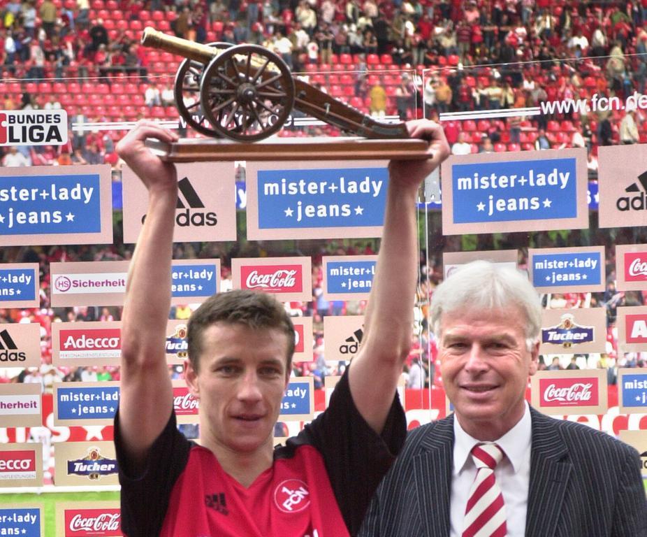Und Marek Mintal arbeitete weiter an seinem Legenden-Status. Im Mai 2005 blickte ganz Fußball-Deutschland in die Frankenmetropole. Mit 24 Treffern, durch welche er den FCN zugleich in Liga eins hielt, war das Phantom - als erster Club-Spieler in der Bundesliga-Geschichte überhaupt - Torschützenkönig geworden. Die Torjägerkanone, welche er als Auszeichnung hierfür vom heutigen kicker-Herausgeber Rainer Holzschuh überreicht bekam, reckt Nürnbergs neue Fußball-Ikone stolz nach oben.