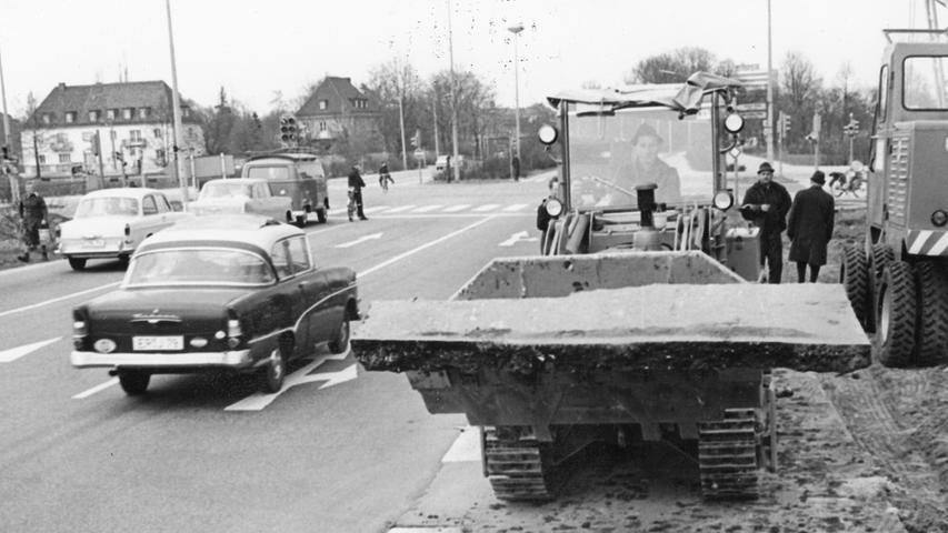 """An der Kreuzung dieser großen Einfahrt von Südosten nach Nürnberg mit der Bayernstraße hat sich durch Abbieger nach rechts und vor allem nach links ein so starker Stau ergeben, daß der Geradeausverkehr in den """"Stoßzeiten"""" ernsthaft behindert wurde. Zum ganzen Artikel: 21. April 1965: Die neue Straße wird aufgerissen."""