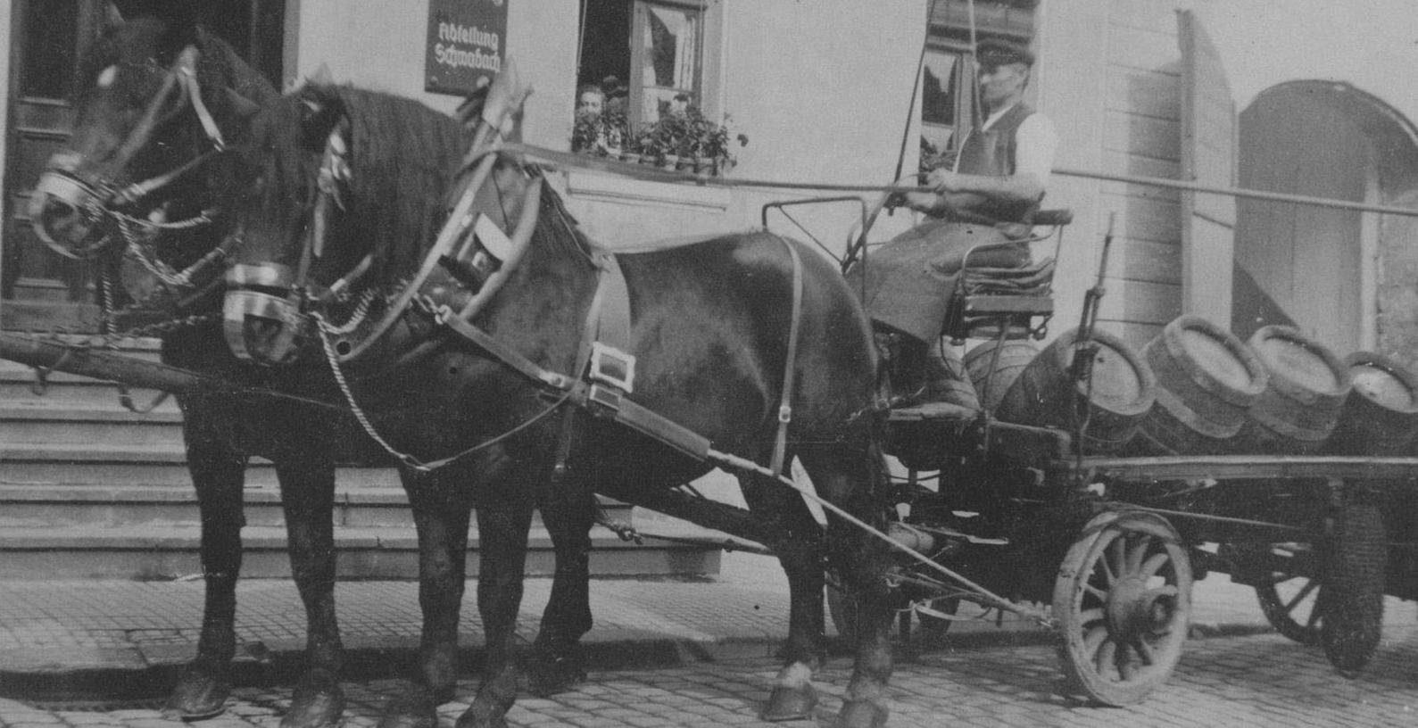 """Heinrich Brechtel mit einem Bierfuhrwerk vor dem Anwesen Hördlertorstraße 14. Er war über 40 Jahre zunächst im landwirtschaftlichen Betrieb und später als Bierkutscher für die Brauerei tätig. Das Foto entstand um 1928. Aus dem Fenster schaut die Haushälterin von Julius Forster. Die Schilder am Haus geben einen Großteil der Geschichte wieder. Über der Tür steht """"Forster-Brauerei"""", rechts daneben """"Brauhaus Schwabach. Aktien-Gesellschaft"""", darunter hängt schließlich ein Schild mit der Aufschrift """"Brauhaus Nürnberg, Abteilung Schwabach""""."""
