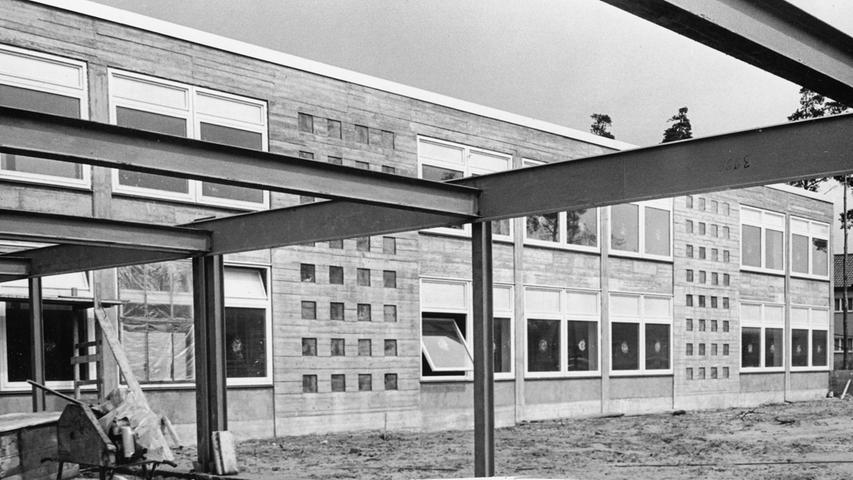 Das ist einer der beiden Pavillons, die nach den Plänen von Architekt Dipl.-Ing. Ferdinand Reubel an der Königshammer Straße gebaut werden. Die Stahlkonstruktion (im Vordergrund) stellt das Gerippe für den Pausenhof dar, der die beiden Schultrakte und die Turnhalle verbindet.