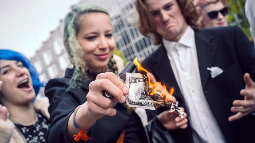 Demonstranten verbrennen am 25.04.2015 in Nürnberg (Bayern) einen unechten 100  US-Dollar Schein. Nürnberger Jugendorganisationen zogen mit ihrer  Satire-Demonstration durch die Nürnberger Innenstadt und kritisierten damit  insbesondere die Geld-Politik. Foto: Nicolas Armer/dpa +++(c) dpa - Bildfunk+++