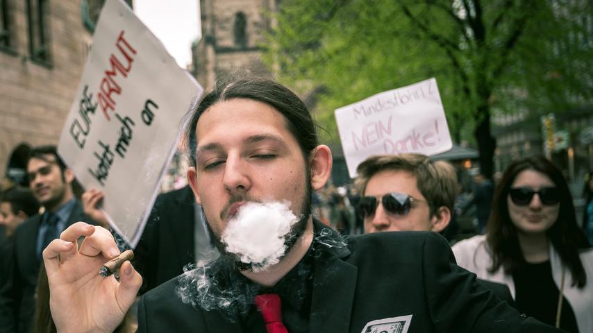 Ein Demonstrant bläst am 25.04.2015 in Nürnberg (Bayern) Zigarrenrauch aus dem  Mund. Im Hintergrund hält ein Mann das Schild