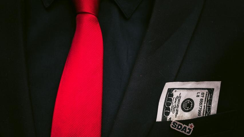 In der Brusttasche eines Demonstranten ist am 25.04.2015 in Nürnberg (Bayern)  ein Anstecker der Sozialistischen Deutschen Arbeiterjugend (SDAJ) und ein  unechter 100 US-Dollar Schein zu sehen. Nürnberger Jugendorganisationen zogen  mit ihrer Satire-Demonstration durch die Nürnberger Innenstadt und kritisierten  damit insbesondere die Geld-Politik. Foto: Nicolas Armer/dpa +++(c) dpa -  Bildfunk+++