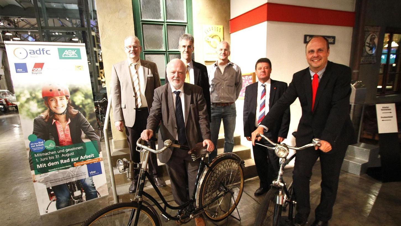 Mit historischen Rädern aus der Sammlung des Museums Industriekultur geben Bürgermeister Christian Vogel (rechts) und Organisationsreferent Wolfgang Köhler (2. von links) mit weiteren Mitstreitern das Startsignal für die Aktion.
