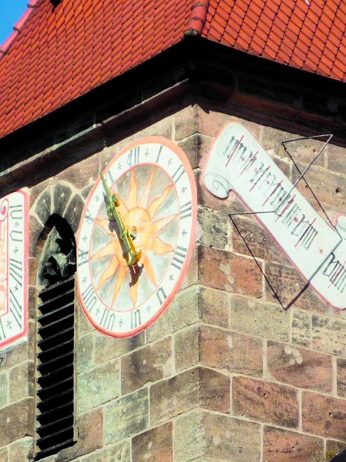 Uhr und Sonnenuhren der Tennenloher Kirche.