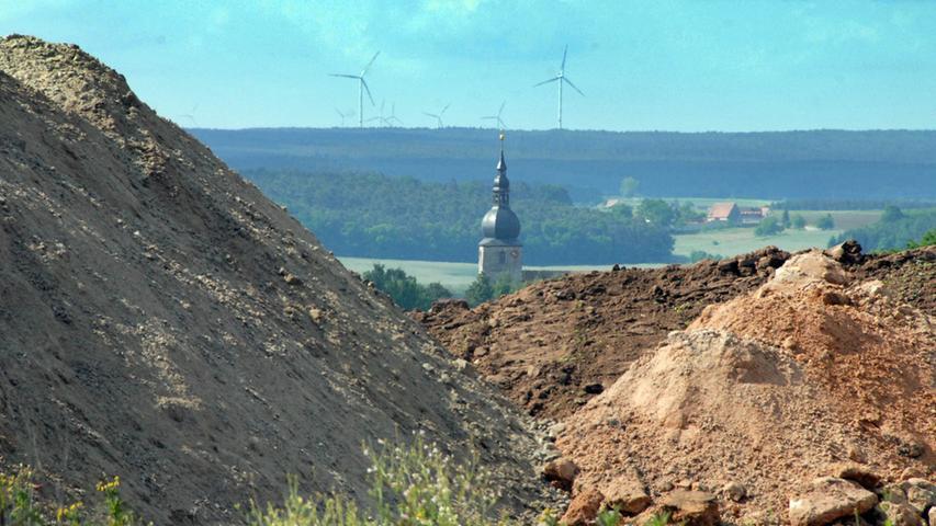 Mai 2015, Windrad 4: Der Bodenaushub im Vordergrund, dahinter der Kirchturm in Lonnerstadt, und im Hintergrund? Das Teleobjektiv holt die Windräder im Landkreis Neustadt/Aisch ganz nah heran.