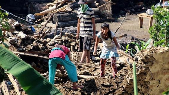 Die Trümmer werden nach verwertbaren Materialien durchsucht.