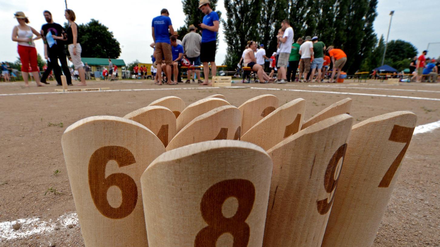 Zwölf Holzklötzchen, ein Ziel: Beim Mölkky versuchen die Spieler exakt 50 Punkte zu erreichen. Trifft man die Kegel mit dem Wurfholz, fliegen sie teils weit auseinander und verteilen sich so auf dem Feld.