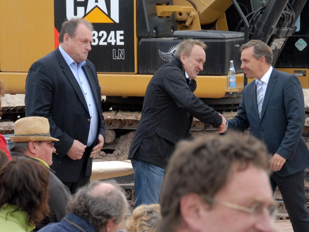 Erster Spatenstich: Viele Besucher waren gekommen, um bei dem feierlichen Ereignis dabei zu sein.  Landrat Alexander Tritthart (r.) wünscht Erich Wust ein guten weiteren Verlauf  der Bauarbeiten. Links Walter Nussel.