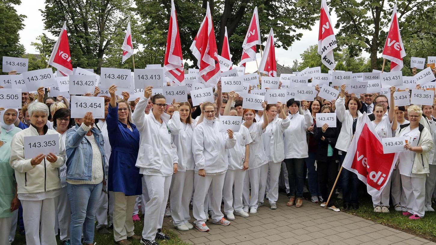 """""""Mehr von uns ist besser für alle"""": Wie in anderen Kliniken in ganz Deutschland hielten die Beschäftigten Karten mit Zahlen zwischen eins und 162 000 in die Höhe."""