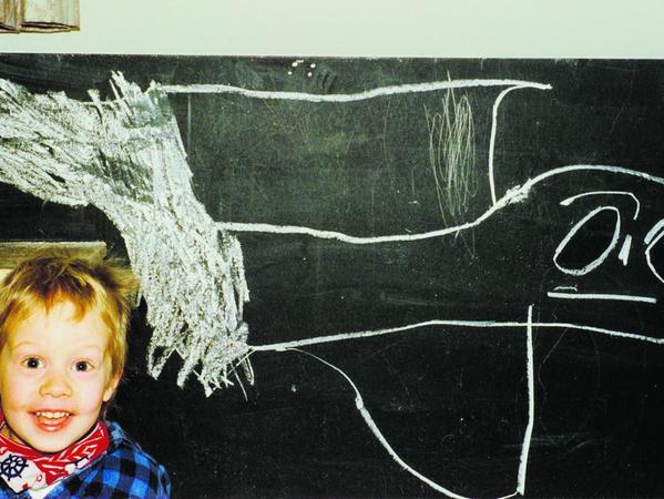Lucas Krieg im Alter von fünf Jahren. Auf die Tafel hat er ein Wesen gezeichnet, das ihm im Traum begegnet ist.