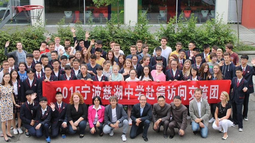"""Zum vierten Mal darf das Schwabacher Adam-Kraft-Gymnasium (AKG) im Juli 2015 eine Delegation seiner chinesischen Partnerschule, der Ningbo Cihu High School, begrüßen. Ningbo, an der chinesischen Ostküste gelegen, gilt mit seinen mehr als fünf Millionen Einwohnern geradezu als Kleinstadt und ist rund 100 Kilometer von der Metropole Shanghai entfernt. Für das AKG, das Chinesisch als spätbeginnende Fremdsprache anbietet, ist vor allem der interkulturelle Austausch zwischen Schülerinnen und Schülern wichtig. Die chinesischen Jugendlichen wohnen eine Woche bei Gastfamilien, erkunden Schwabach und Umgebung. Ferner können die Gäste ihre Deutschkenntnisse anwenden, denn seit einem Jahr gibt es an der Cihu High School die Möglichkeit, Deutsch zu lernen. Die Verbindungen zum """"Land des Lächelns"""" haben auch über die Schulzeit hinaus Bestand, zwei Absolventen des diesjährigen Abiturjahrgangs erhielten ein Stipendium des Konfuzius-Instituts, um ein halbes Jahr an der Universität der Partnerstadt Nürnbergs, Shenzen, zu studieren. Die AKG-Schüler fiebern dem Gegenbesuch im Oktober entgegen, dann werden sie ihre Austauschpartner an der Schule begleiten und eine China-Rundreise unternehmen."""