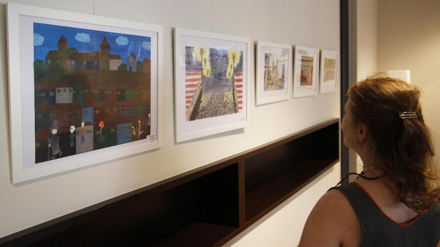 """Eine Besucherin der Ausstellung des Mein-Nürnberg-Wettbewerbs ganz im Bann von Alyie Cetins farbenfrohem Bild """"Nürnberg nach James-Rizzi-Art"""" (ganz links).Foto: Eduard Weigert"""